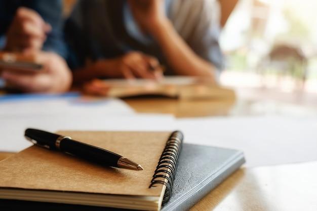 Koncepcja edukacji. student studiuje i burzy mózgów koncepcji kampusu. zamknij studentów omawiających ich tematy na książkach lub podręcznikach. selektywne fokus.