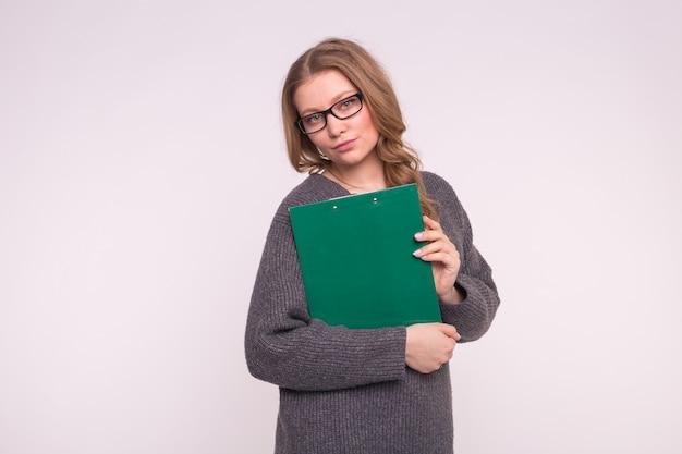 Koncepcja edukacji, studentów i ludzi. kobieta na białym ubrana w szary sweter trzymać papierową teczkę.