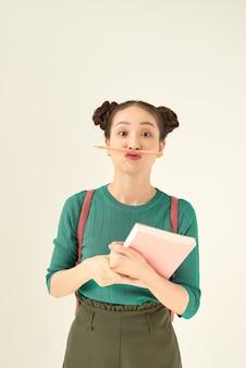 Koncepcja edukacji, szkoły, inspiracji i ludzi - młoda kobieta lub nastoletnia studentka w zielonej koszulce z pamiętnikiem lub notatnikiem i ołówkowym wąsem na jasnozielonym tle