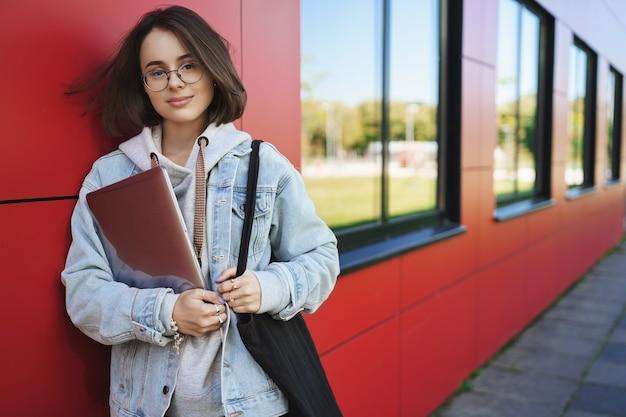 Koncepcja edukacji, uczenia się i młodzieży. odkryty portret rozmarzonej, zamyślonej młodej kobiety w okularach, trzymając laptopa jako zajęcia końcowe, kierując się do przestrzeni coworkingowej, pracując jako wolny strzelec, uśmiechając się do kamery.