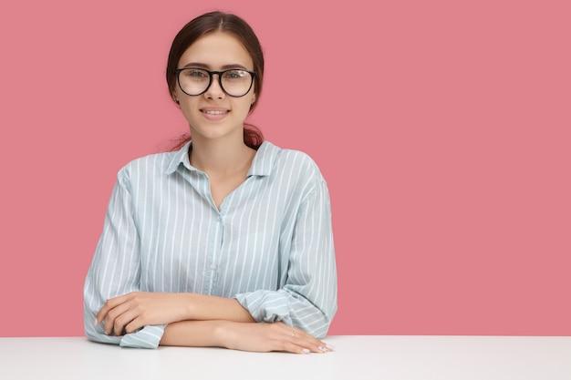Koncepcja edukacji, uczenia się, wiedzy i ludzi. piękny przyjazny wyglądający młoda kobieta kaukaski noszenie stylowych okularów i niebieskiej koszuli siedzi przy biurku, gotowy do nauki