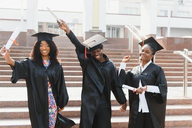 Koncepcja edukacji, ukończenia studiów i ludzi - grupa szczęśliwych międzynarodowych studentów w tablicach z zaprawą i kawalerskich sukniach z dyplomami