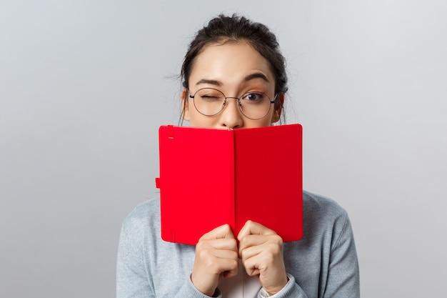 Koncepcja edukacji, uniwersytetu i ludzi. close-up portret bezczelnej studentki azjatyckiej, mrugnięcie zachęca kolegów z klasy, aby zdali egzamin, chowają usta za planistą, studiują, piszą tajny pamiętnik