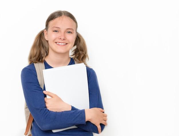 Koncepcja edukacji uśmiechnięta nastolatka z zeszytami i plecakiem na szarym tle