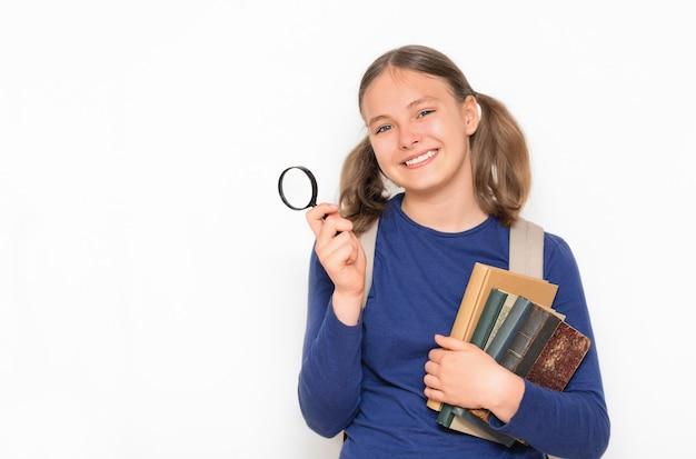 Koncepcja edukacji uśmiechnięta uczennica z lupą i stosem książek na szarym tle
