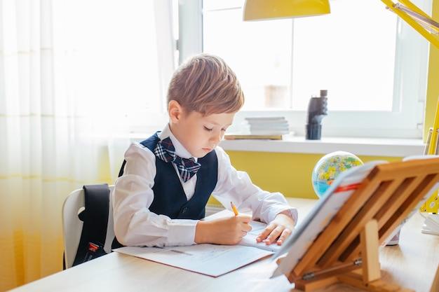 Koncepcja edukacji w domu - śliczny chłopiec studiuje lub uzupełnia domową pracę na stole do nauki z stosem książek, edukacyjnej kuli ziemskiej i skoroszytem