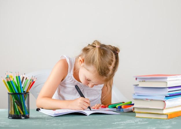 Koncepcja edukacji z widokiem z boku przybory szkolne. mała dziewczynka rysunek na zeszyt.