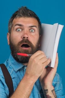 Koncepcja edukacji zaskoczyła ucznia z brodą i wąsami w niebieskiej koszuli, trzyma notatnik i długopis w