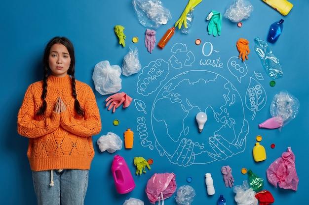 Koncepcja ekologii i ochrony gruntów. smutna azjatka stoi w pozie do modlitwy, otoczona plastikowymi odpadami, błaga o pomoc w sprzątaniu ziemi, ubrana niedbale