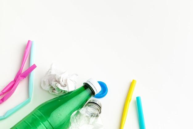 Koncepcja ekologii zagrożenia odpadami z tworzyw sztucznych ze śmieciami i kolorowe jednorazowe słomki, kubki na sztućce, butelki
