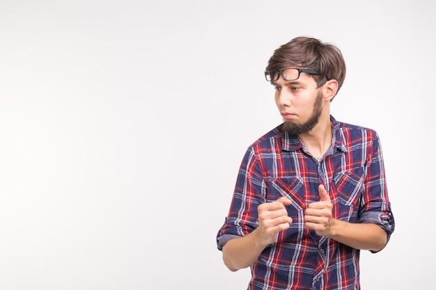 Koncepcja ekspresji i gest - młody brodaty mężczyzna w koszuli w kratę na białej ścianie z kopią