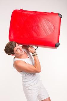 Koncepcja ekspresji i gest - młody człowiek w białej koszuli, trzymając czerwoną walizkę
