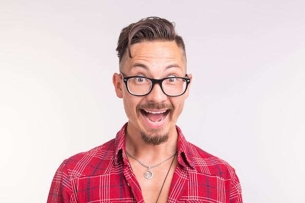 Koncepcja ekspresji i gest - przystojny mężczyzna w okularach, śmiejąc się na białym tle