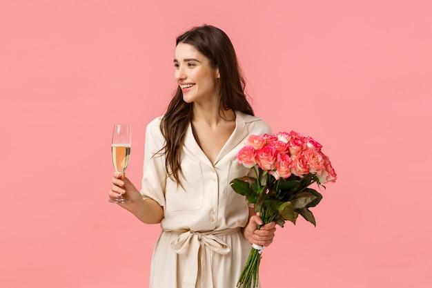 Koncepcja elegancji, uroczystości i imprezy. atrakcyjna młoda szczęśliwa kobieta ma urodziny, otrzymuje prezenty, piękne kwiaty, trzyma róże i kieliszek szampana, uśmiecha się po lewej stronie.