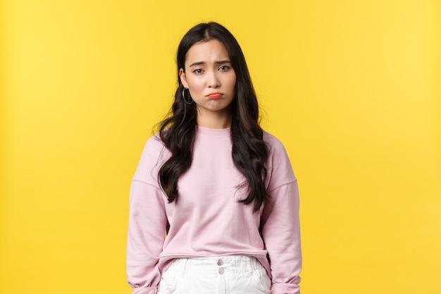 Koncepcja emocje, styl życia i moda ludzi. przygnębiona i smutna, ponura koreańska dziewczyna nadąsająca się, patrząca w dół na wysypiska, zdenerwowana i niezadowolona, stojąca na żółtym tle.
