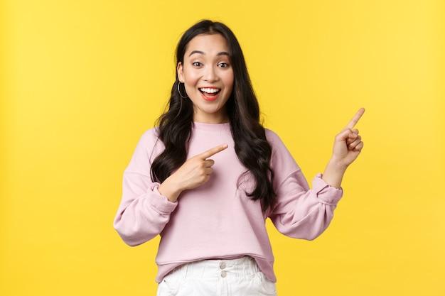 Koncepcja emocje, styl życia i moda ludzi. uśmiechnięta studentka pokazująca oferty wakacji, specjalne promocje lub rabaty w sklepie, wskazując palcem w prawo i uśmiechnięte, żółte tło.