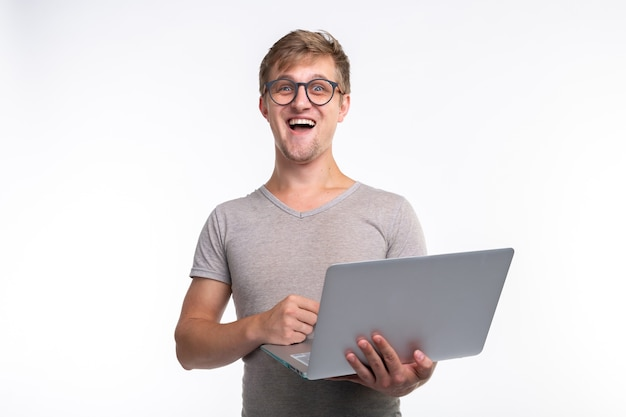 Koncepcja emocji, edukacji i ludzi - młody przystojny mężczyzna, patrząc w laptopa i śmiejąc się