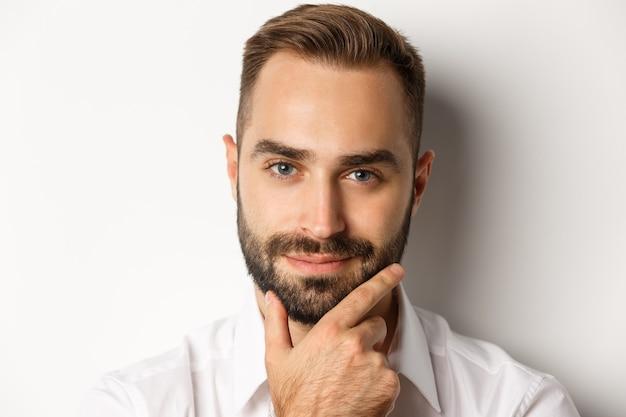 Koncepcja emocji i ludzi. headshot przystojny, zamyślony mężczyzna uśmiecha się zadowolony, dotyka brody i myśli, stoi