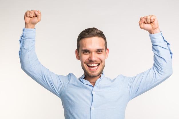 Koncepcja emocji i ludzi - młody szczęśliwy człowiek uniósł pięści nad białą ścianą.