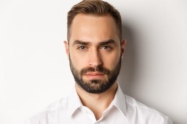 Koncepcja emocji i ludzi. zdjęcie w głowę poważnie wyglądającego przystojnego mężczyzny z brodą, pewnego siebie i zdecydowanego