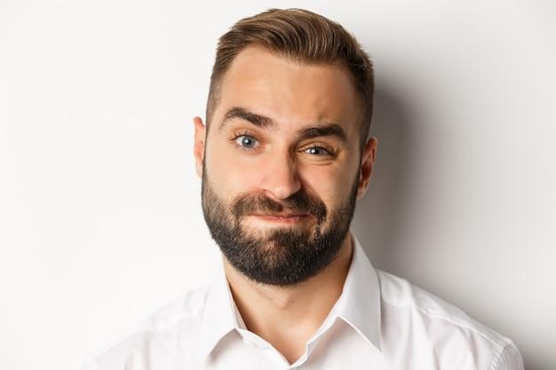 Koncepcja emocji i ludzi. zdjęcie w głowę sceptycznego mężczyzny z brodą, grymasującego i wyglądającego na wątpliwego, stojącego niezadowolonego