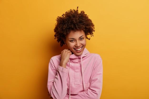 Koncepcja emocji, młodzieży i ludzi. rozbawiona ładna kobieta szczerze się śmieje, ma nieśmiały wyraz twarzy, ma ciekawy pomysł, trzyma rękę na bluzie, cieszy się życiem, pozuje w domu na żółtej ścianie