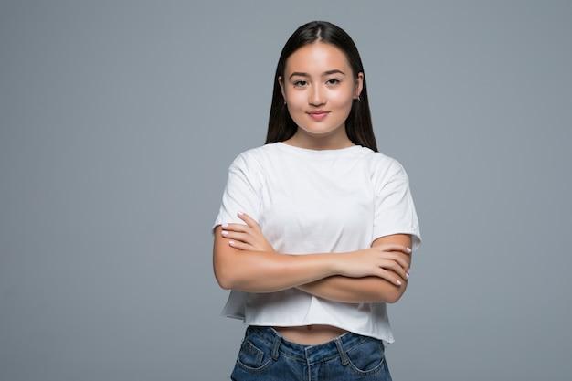 Koncepcja emocji. portret gniewna śliczna azjatykcia kobiety pozycja pozuje z krzyżować rękami patrzeje kamerę z popielatym odziewa na białym tle