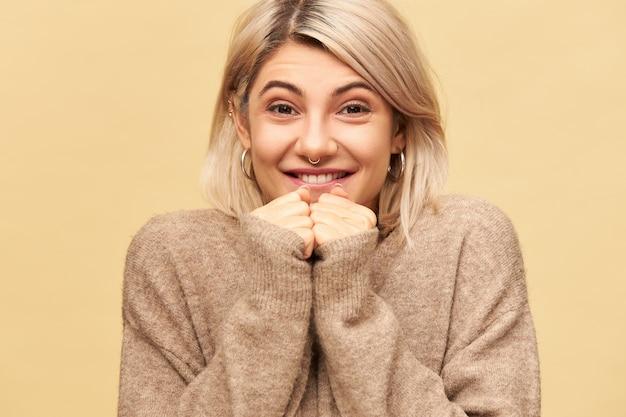 Koncepcja emocji, przyjemności i pozytywnego nastawienia. na białym tle obraz dobrze wyglądającej stylowej ładnej dziewczyny sobie przytulny sweter zaciskając pięści na jej twarzy i uśmiechając się, przewidując coś niesamowitego