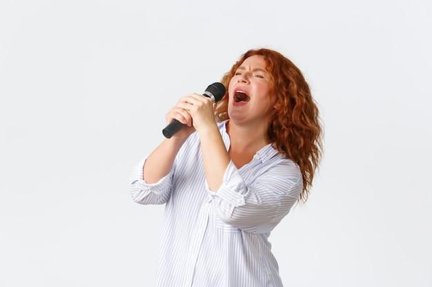 Koncepcja emocji, stylu życia i wypoczynku. namiętna i beztroska rudowłosa performerka, kobieta w średnim wieku śpiewająca piosenkę do mikrofonu, piosenkarka grająca w karaoke, białe tło.