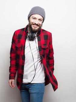 Koncepcja emocjonalna i ludzi: młody brodaty mężczyzna w kapeluszu ze słuchawkami