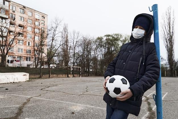 Koncepcja epidemii i kwarantanny - samotny chłopiec z maską na twarz i piłką na boisku sportowym w mieście