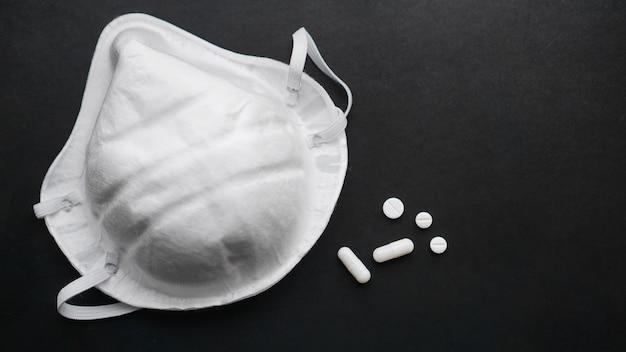 Koncepcja epidemii i wirusa - białe pigułki i maski na czarnym tle