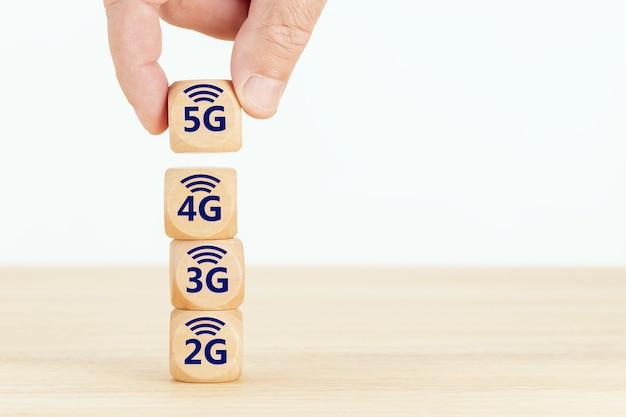 Koncepcja ewolucji sieci 5g. dłoń trzymająca drewniany blok z tekstem i symbolem.