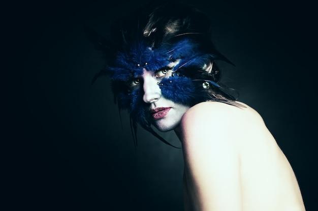 Koncepcja fantazji. kobieta z art makeup. fantazja niebieski ptak. makijaż sceniczny