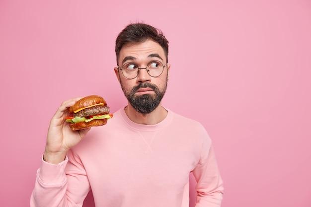Koncepcja fast foodów. głodny brodaty mężczyzna trzyma apetycznego hamburgera, który będzie miał niezdrową, pyszną przekąskę, która wygląda zaskakująco z dala, ubrany niedbale pozuje przed różową ścianą, puste miejsce na tekst