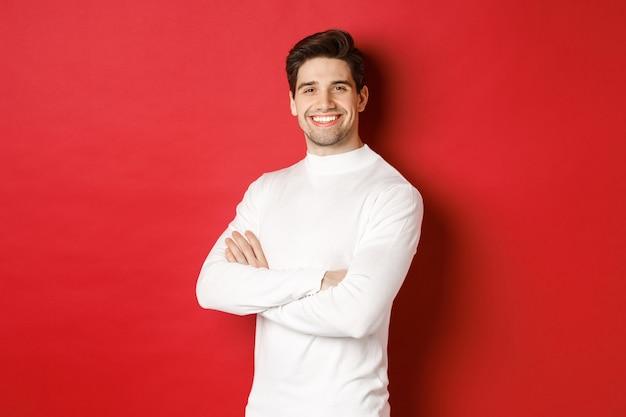 Koncepcja ferii zimowych boże narodzenie i styl życia portret pewny siebie atrakcyjny facet w białym sweterku...