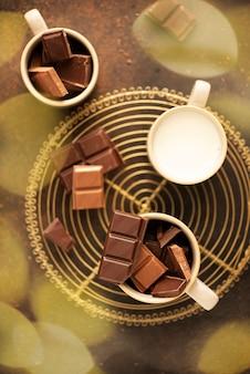 Koncepcja ferii zimowych. kawałki czekolady i mleka gotowe do przygotowania gorącego napoju czekoladowego.