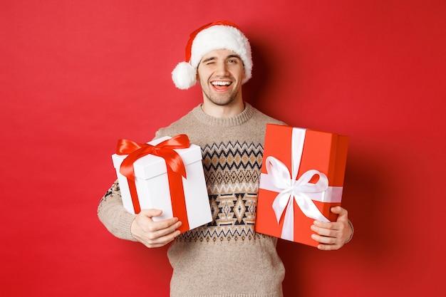Koncepcja ferii zimowych, nowego roku i uroczystości. portret pewnego siebie i bezczelnego młodego mężczyzny przygotował prezenty na boże narodzenie, mrugając i trzymając prezenty, stojąc na czerwonym tle
