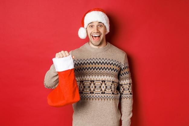 Koncepcja ferii zimowych, nowego roku i uroczystości. wesoły i zaskoczony dorosły mężczyzna odbiera cukierki w dzień świętego mikołaja w czerwonej pończochach, stojąc zdumiony na czerwonym tle.