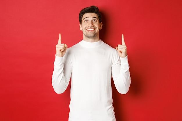 Koncepcja ferii zimowych obraz szczęśliwego, atrakcyjnego mężczyzny w białym swetrze, uśmiechniętego, wskazującego i...