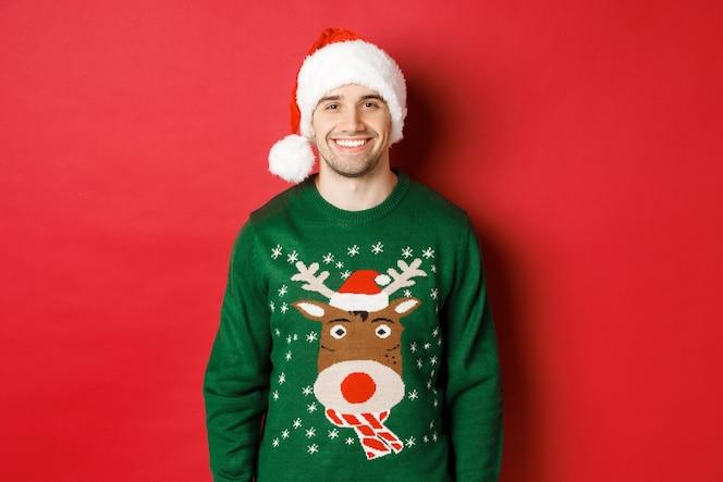 Koncepcja ferii zimowych, świąt bożego narodzenia i stylu życia. przystojny facet z włosiem, w czapce mikołaja i zielonym swetrze, uśmiechnięty radośnie, świętujący nowy rok, stojący na czerwonym tle.