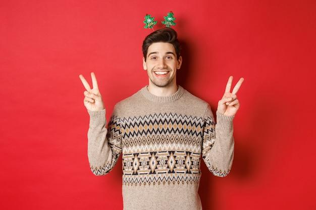 Koncepcja ferii zimowych, świąt bożego narodzenia i uroczystości. obraz przystojnego i głupiego faceta ubranego na przyjęcie sylwestrowe, pokazującego znaki pokoju i uśmiechniętego, stojącego na czerwonym tle