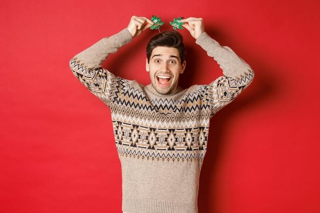 Koncepcja ferii zimowych, świąt bożego narodzenia i uroczystości. obraz zabawny i uroczy dorosły mężczyzna cieszący się przyjęciem sylwestrowym, uśmiechnięty i radujący się, stojący na czerwonym tle.
