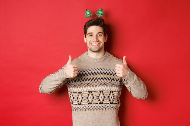 Koncepcja ferii zimowych, świąt bożego narodzenia i uroczystości. wesoły brodaty facet w swetrze, pokazując kciuk do góry z aprobatą i uśmiechnięty, ciesząc się przyjęciem sylwestrowym, czerwone tło