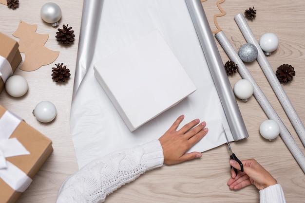Koncepcja ferii zimowych - zbliżenie kobiecych rąk pakujących prezenty świąteczne na drewnianym stole