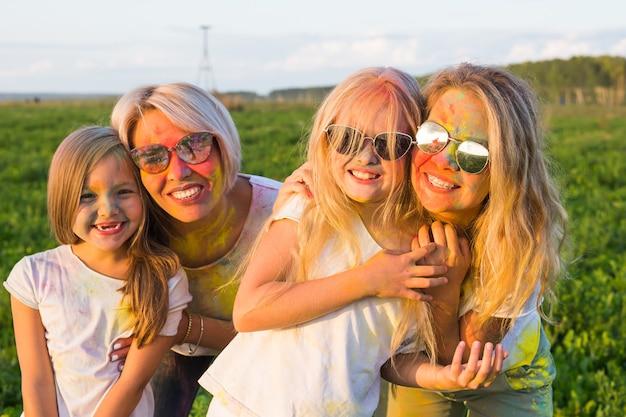 Koncepcja festiwalu holi, przyjaźni, szczęścia i wakacji - małe dziewczynki i kobiety w okularach przytulające się na festiwalu holi