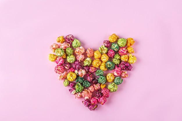 Koncepcja filmów miłości. kolorowe tęczowe cukierki karmelowe popcorn rozrzucone na różowym tle, z bliska w kształcie serca, kopia miejsca na tekst. koncepcja przekąsek kinowych