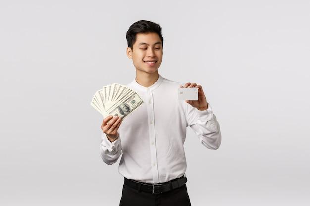 Koncepcja finansów, gospodarki i biznesu. przystojny azjatykci biznesmen w formalnym stroju, trzymający gotówkę i kredytową kartę, patrzejący bankowości płatniczą metodę z zadowolonym uśmiechem, wydaje pieniądze
