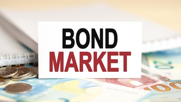Koncepcja finansów i ekonomii. na stole banknoty, monety i biały znak na którym jest napisane - rynek obligacji