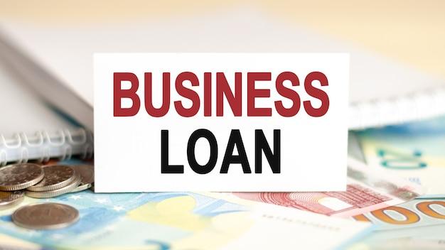 Koncepcja finansów i ekonomii. na stole rachunki, monety i biały papier, na którym jest napisany - pożyczka biznesowa.